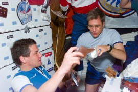 "(Local Identifier: 255-STS-S79E5242) ""Mir 22 commander Valerie Korzun makes a selection from various food packets with the help of astronaut John Blaha . They and the other members of the STS-79 and Mir 22 crews are sharing a barbecue dinner on the Atlantis's middeck"""