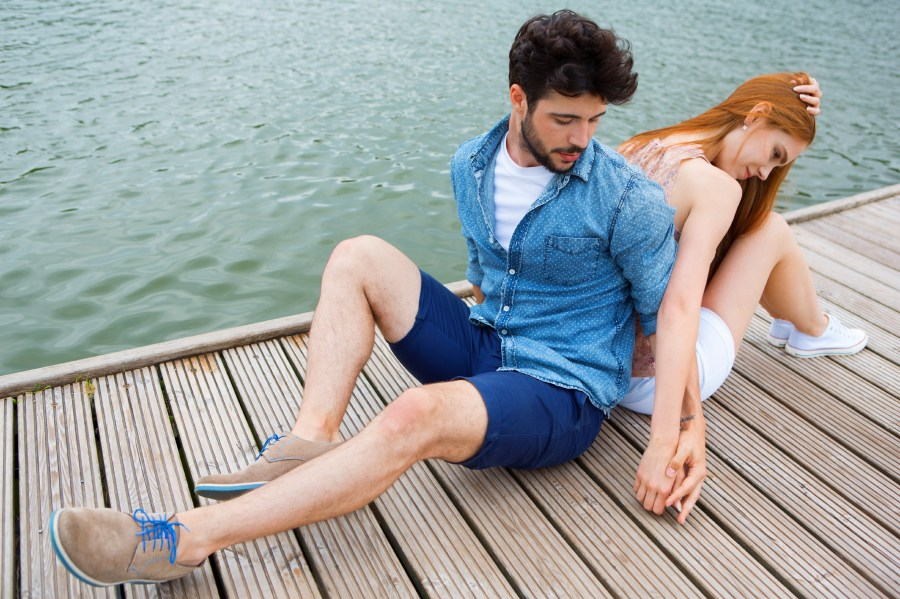 Young couple on jetty reconciling after quarrel
