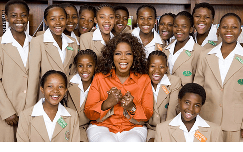 Oprah Winfrey posing with students at her Leadership Academy; she and the students smile, and she holds two students' hands.