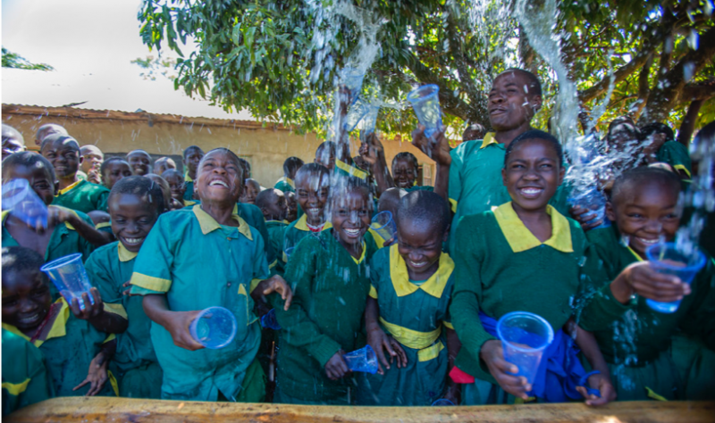 School children in uniforms throwing cups of water into the air.
