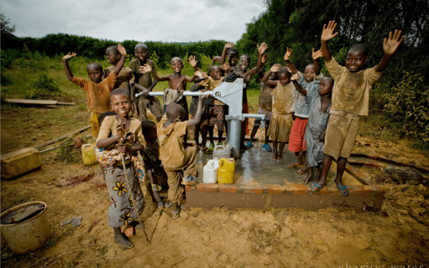 A group of children in Rwanda surround a newly finished charity:water well project and celebrate.