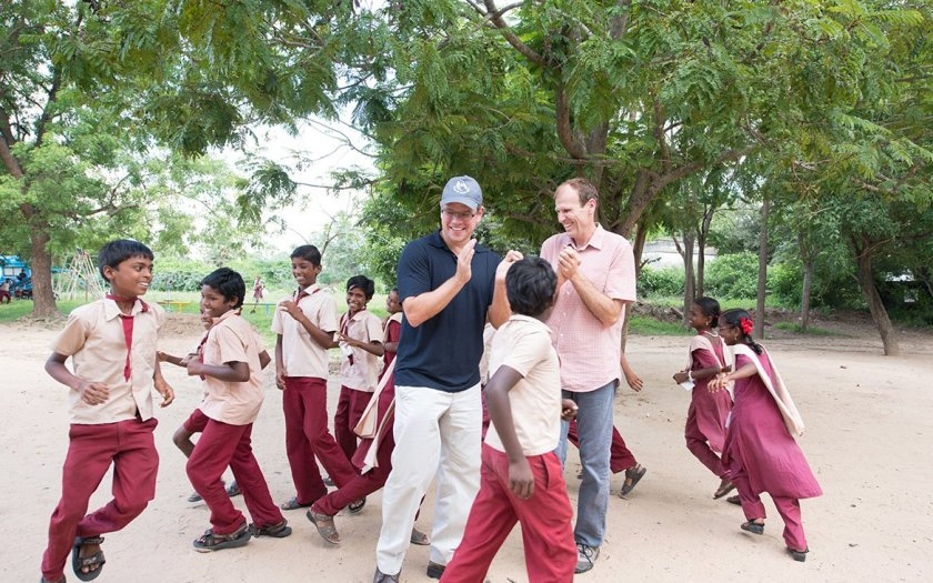 Matt Damon and Gary White, co-founders of Water.org, clap as a group of children dances in a circle around them.