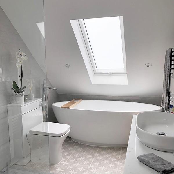 A small, modern white bathroom with an exempt bathtub