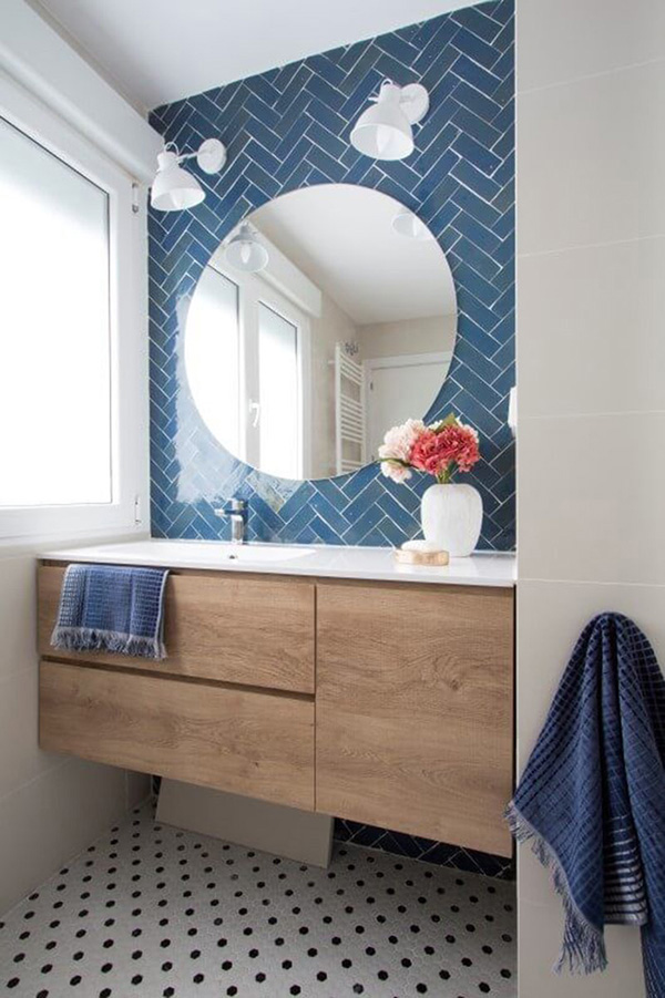 A small bathroom with blue metro type tile and round mirror