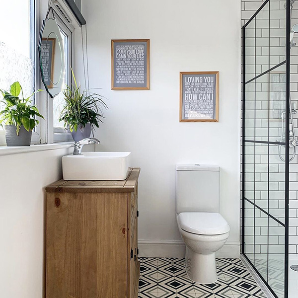 A small bathroom with a black metal screen with glass frames.