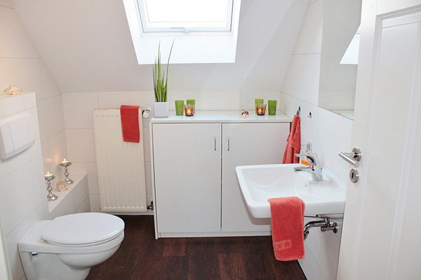A small white bathroom with red and green details
