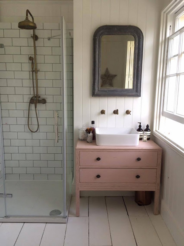 A small bathroom with a pink furniture
