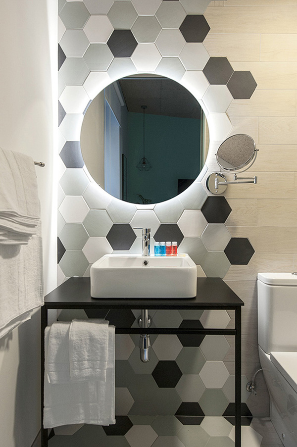 A small bathroom with hexagonal tile and a backlit round mirror