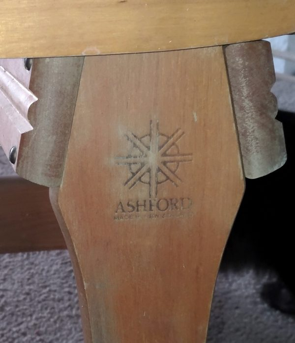 Closeup of part of the spinning wheel, which says Ashford.