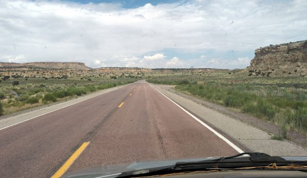 Another shot from behind the wheel, the road leading through & between mesas.