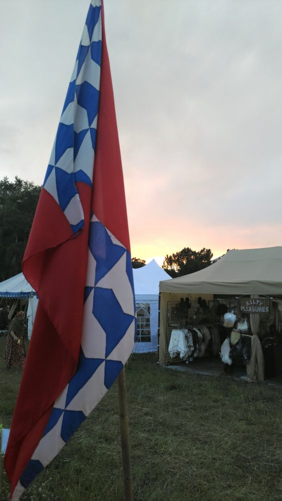 An SCA banner in red, white, & blue waves in front of the last vestiges of a yellow-fading-to-purple sunset.