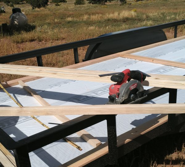 A bunch of 2x2 boards laying across the trailer railings. Also a circular saw.