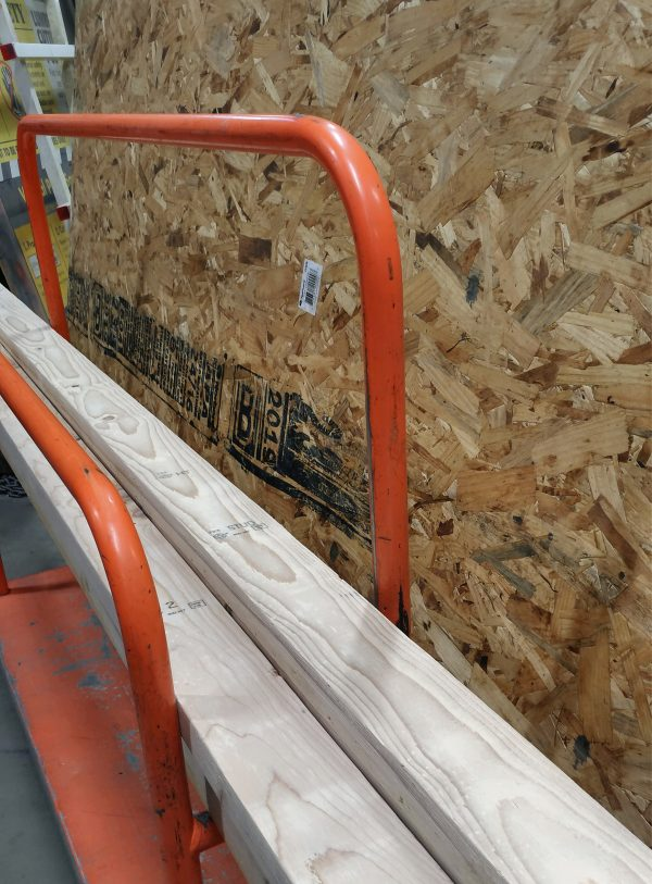 Yet another orange lumber cart, holding yet another load of wood -- this time a sheet of OSB & a bunch of 2x4s.