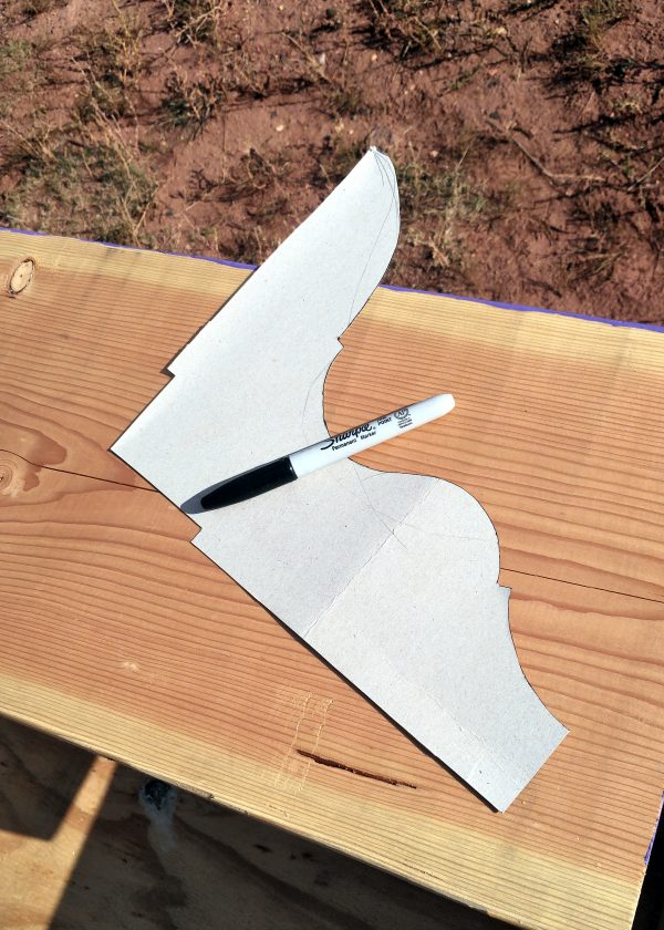 A white piece of cardoard with a sharpie sitting on it. The shape is two straight edges at right angles, with the third side curved in a decorative fashion.