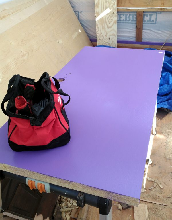 A door lays on a table in the middle of the tinker's wagon. It's vigorously purple, & there's a red toolbag sitting on it.