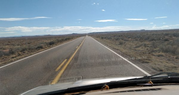 A two-lane road leads straight through flat, scrubby desert under a blue sky, all seen from inside the van.