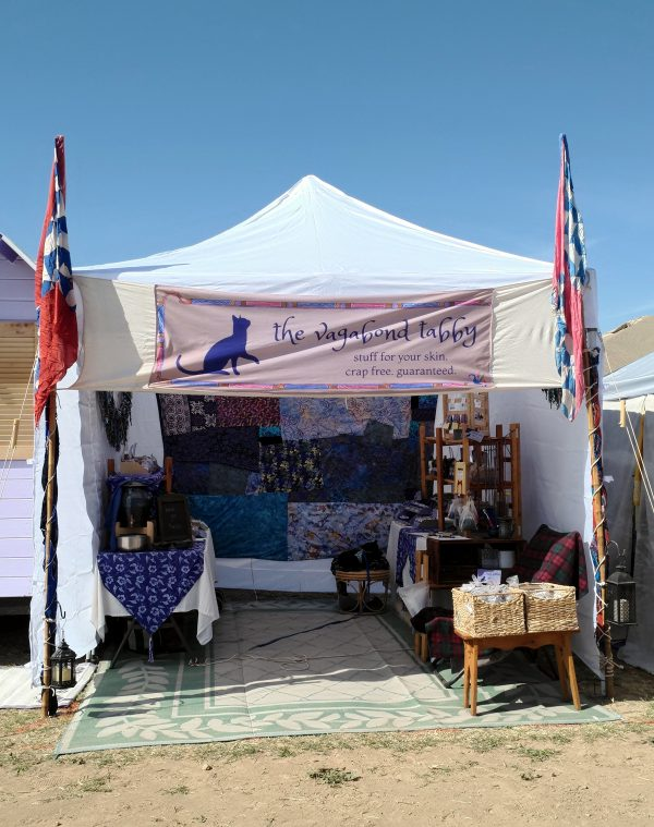 Red, white, & blue banners (but not American flags) fly on either side of the booth. Within, a crazy quilt in blues & purples covers the back wall. A table stands along each side wall, each filled with treasures.