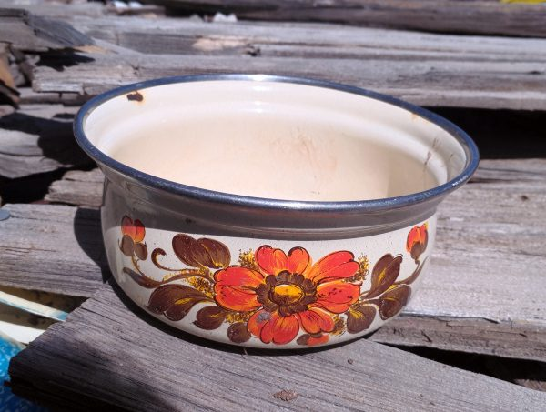 A small cooking pot, enameled in white with an orange flower & brown leaves painted on the side. Very 70s.