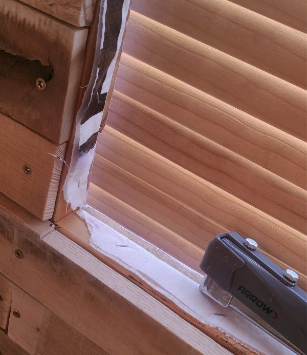 The housewrap has, indeed, been folded down so it runs along the inside edge of the window. I love my staple hammer.