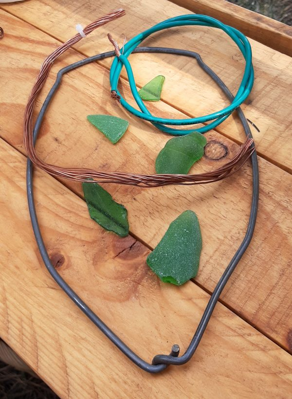 On a wood table: five pieces of green sea glass, a metal bucket handle with the two ends that would go into the top of the bucket twined together, & two buncldes of different thicknesses of copper wire, one enclosed in a teal-blue coating.