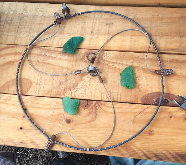 The ends of each length of cable have been attached, with copper wire, to the three bumps in the round bit. The piece that joins them sits at the center, so they make sort of a bumpy triskele. A piece of green seaglass sits inside each section.