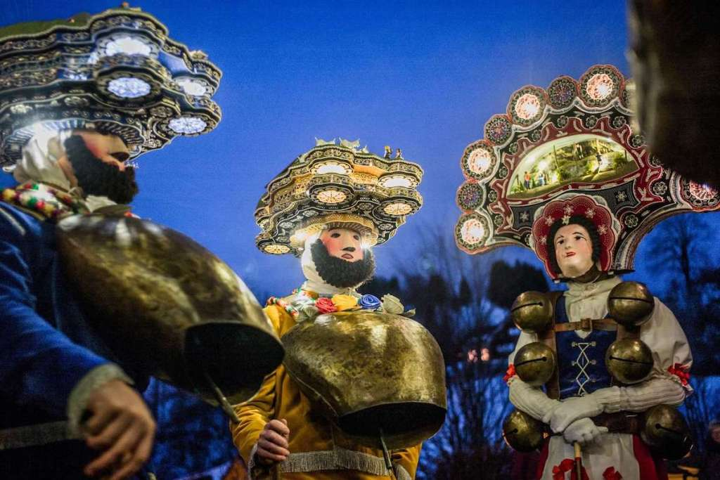 """Groups of elaborately costumed men yodeling and dancing their way from farmhouse to farmhouse during the winter festival """"Silvesterchläusen"""" in Switzerland."""