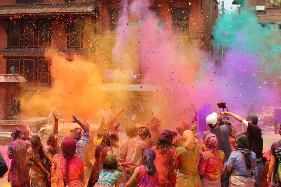People celebrating the Holi Festival of Color, throwing colored powders, in India.