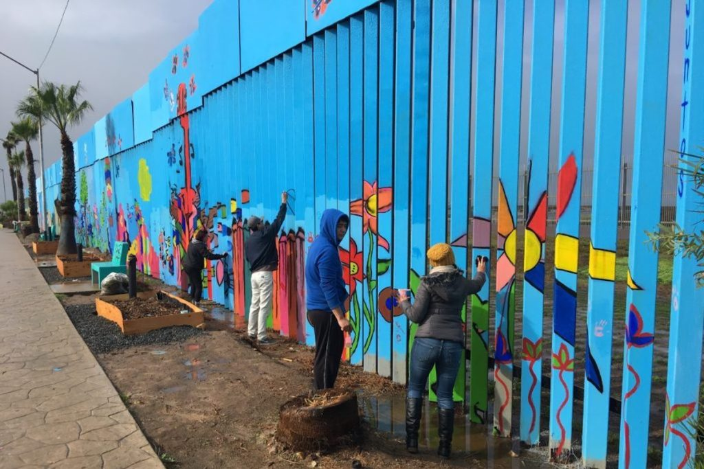Volunteers painting a section of the Mural of Brotherhood project on the US-Mexico border wall.