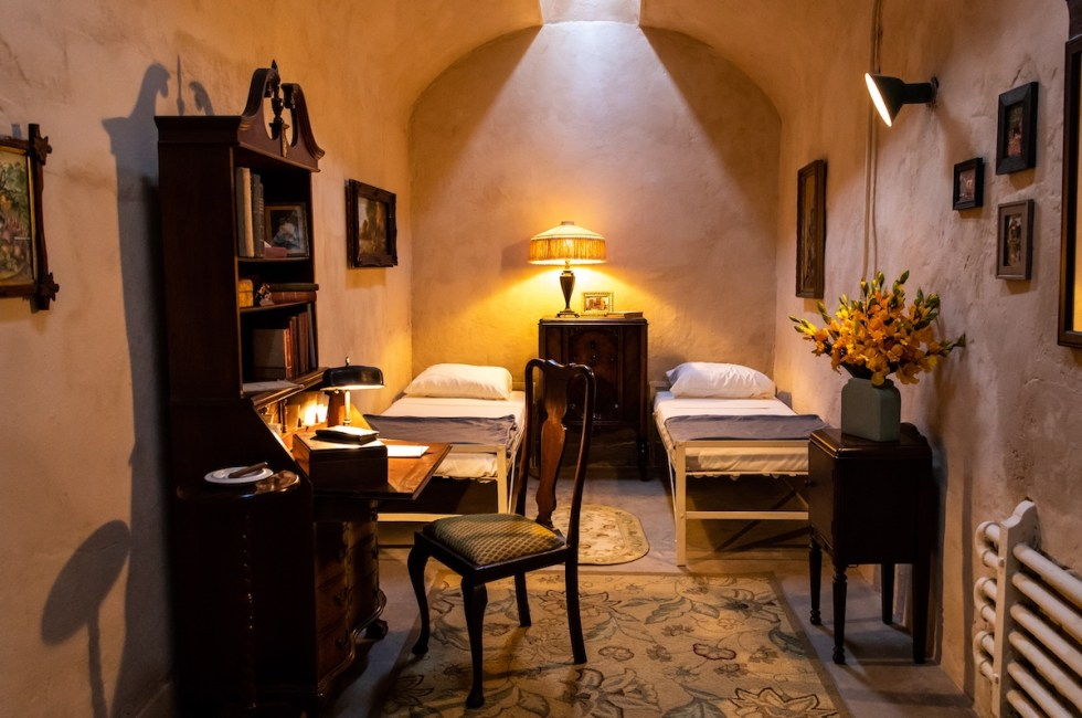 Prison cell with furniture, oil paintings, and other decorative items