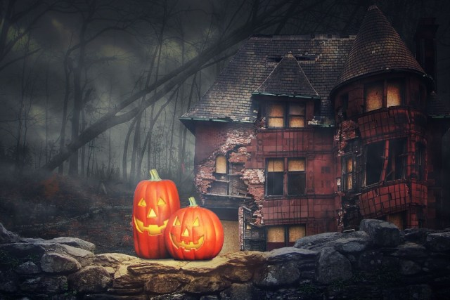 Two jack-o'-lanterns outside an abandoned house in the woods