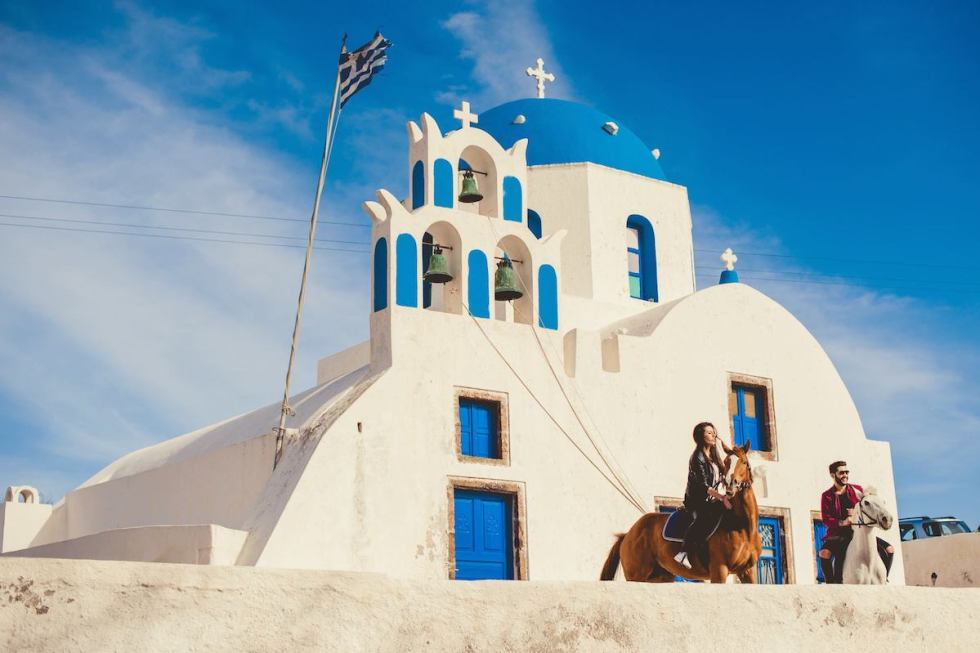 Young couple riding horses outside a church in Santorini, Greece