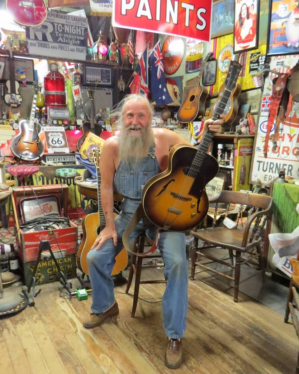Harley Russell posing with a guitar inside Sandhills Curiosity Shop in Erick, Oklahoma