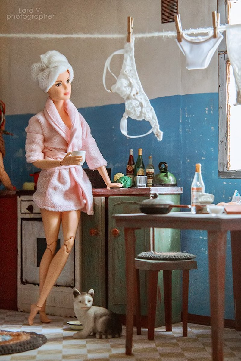 Wearing a plush bathrobe and a towel turban, Barbie is depicted hanging her delicates on a clothesline, sipping coffee and gazing thoughtfully out of the window with a feral looking pup at her feet