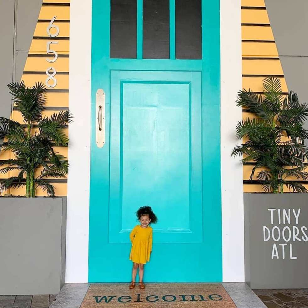 Young girl posing in front of Door #658, part of Tiny Doors ATL project
