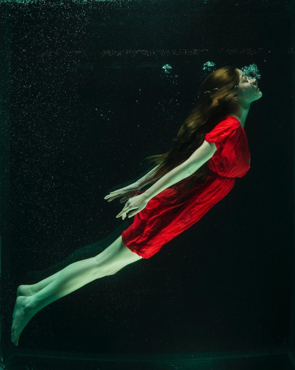 woman wearing red dress underwater