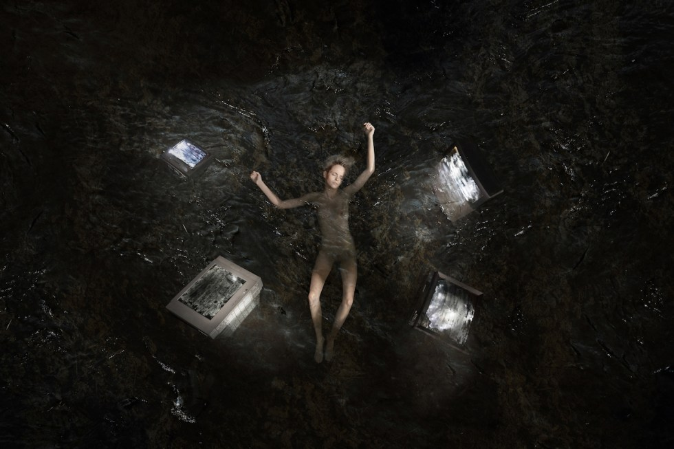 Naked woman submerged in water surrounded by four TV devices