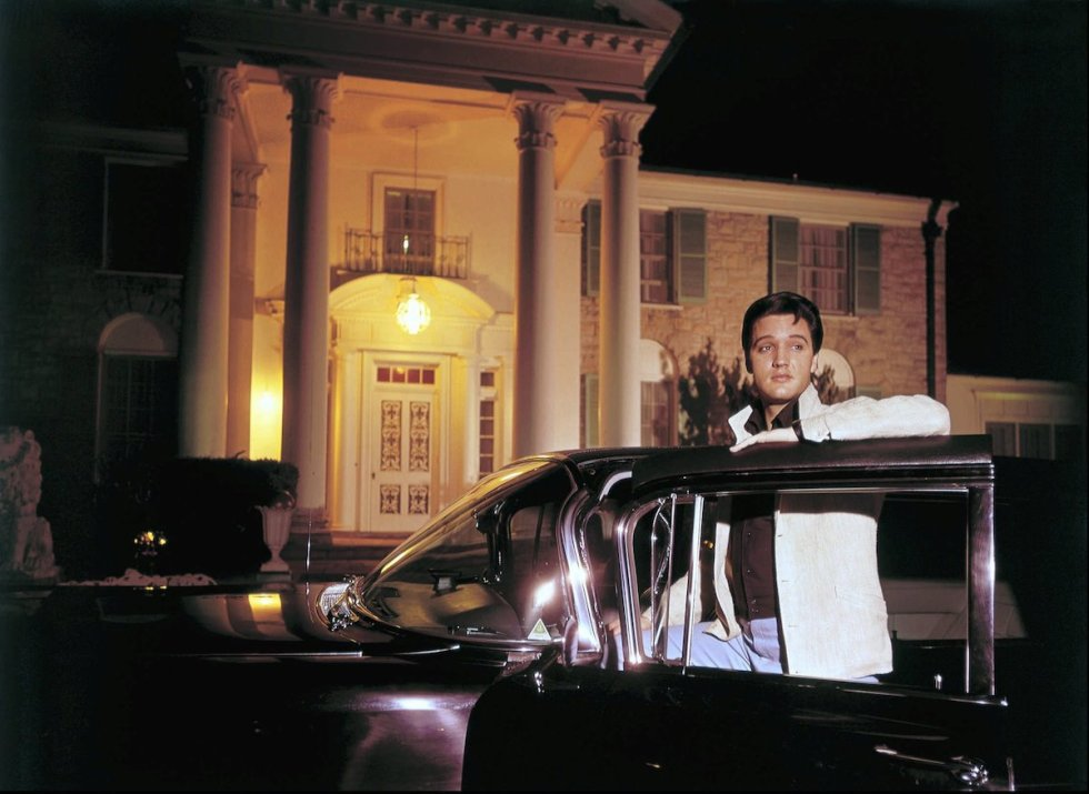 Elvis Presley posing with one of his cars outside Graceland