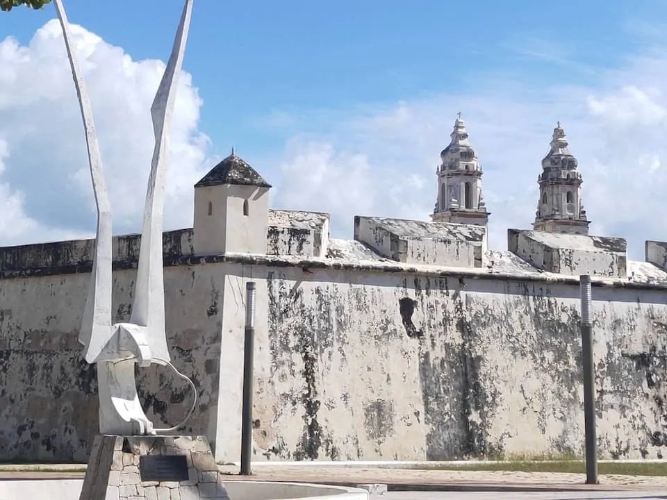 A modern sculpture lies outside the old city walls, the spires of the cathedral can be seen behind the walls.