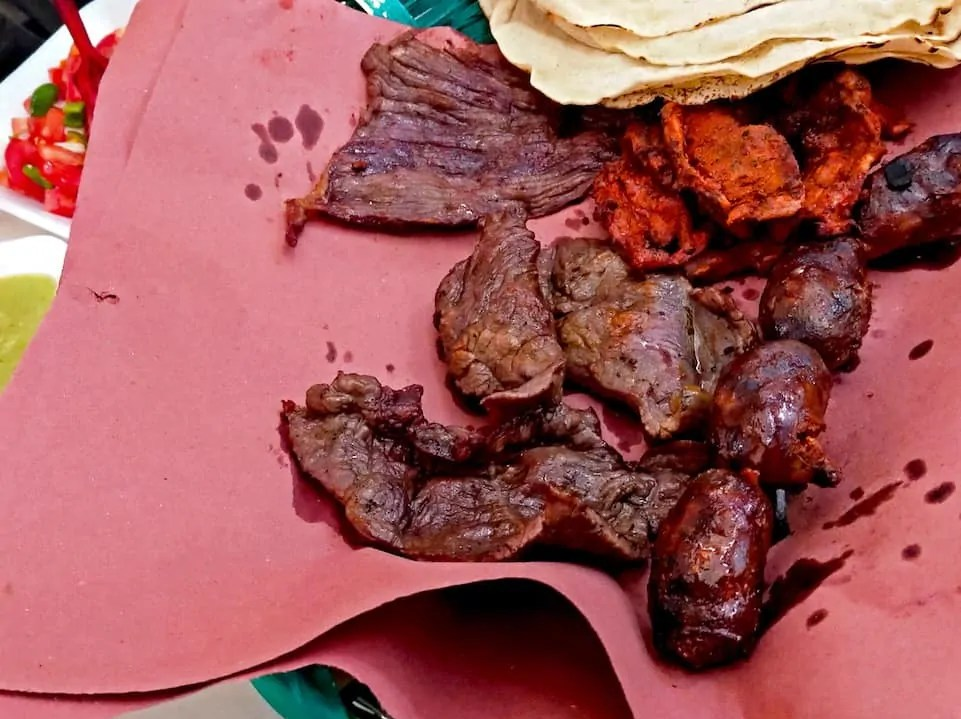 The meat platter of chorizo, skirt steak, and chicken at Mercado 20 de Noviembre in Oaxaca. Where to eat in Oaxaca