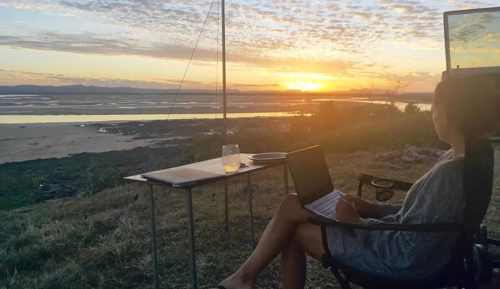 A girl on her laptop with a small table in front of her overlooking the seaa at low tide and the sun set at Notch Point Campground which free camping Queensland.