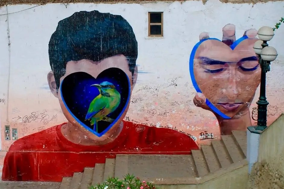 Street art of a boy with his face in the shape of a heart in his hand and a bird in the outline of the hear where his face is.