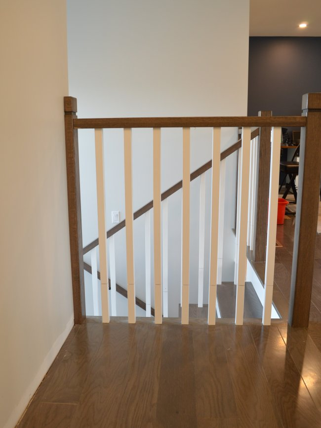 Dark wood handrail with white spindles