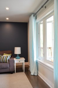 blue and green living room with industrial curtain rod