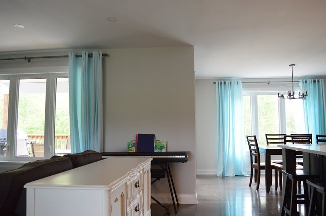 open concept living space with aqua blue curtains