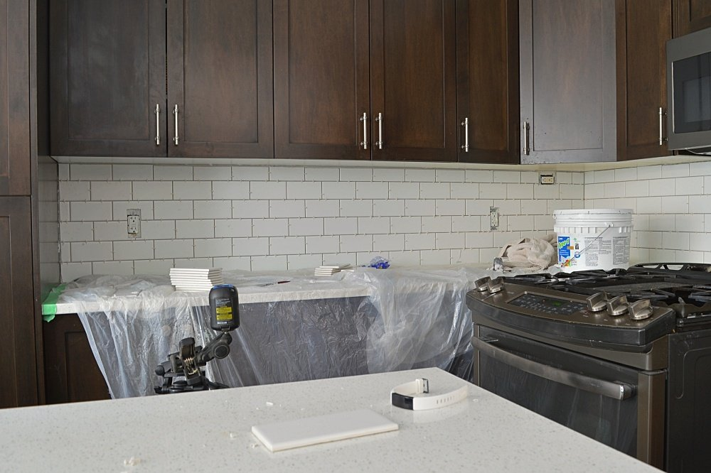white subway tile with dark wood cabinets