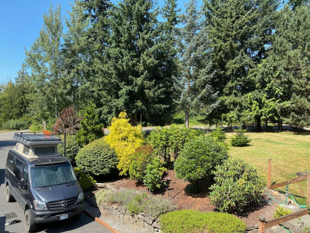 Pop top Mercedes Sprinter van parked in driveway with surrounding trees and garden.