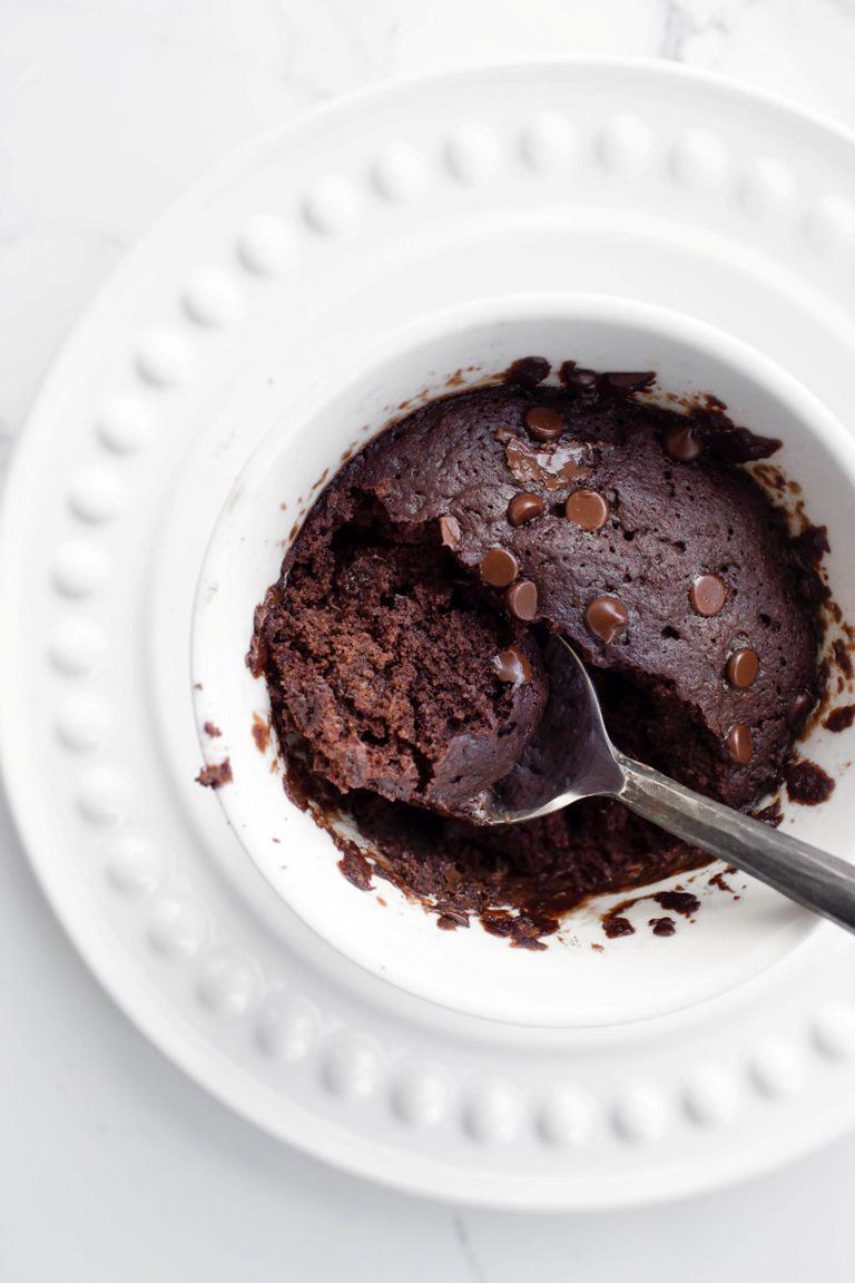 Cooked vegan chocolate mug cake with spoon inside