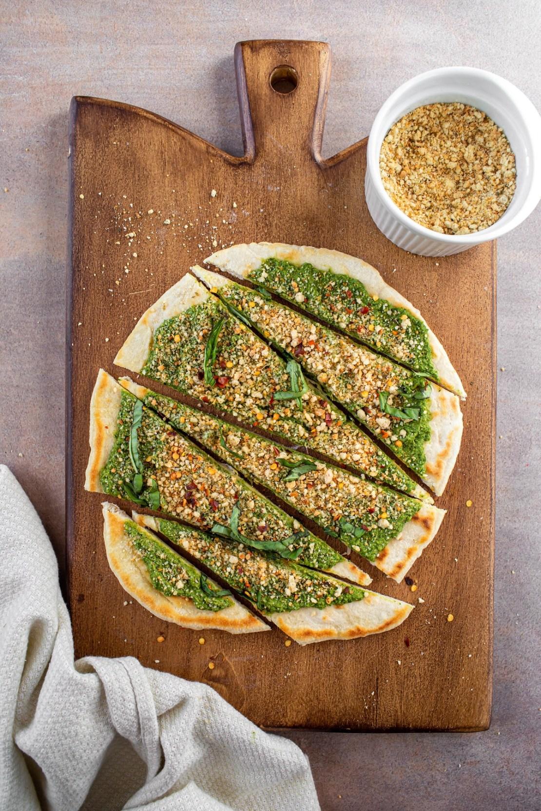 pesto on flatbread with vegan parmesan cheese on wood platter