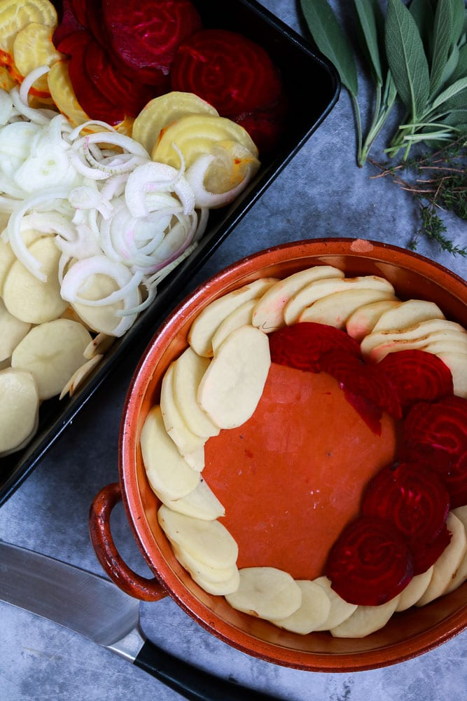 layering the beetroot and potato slices into the dish.