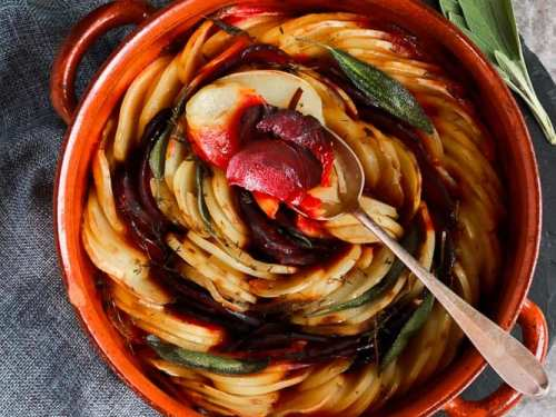 Beetroot and potato boulanger in a beautiful pot with a spoon on top